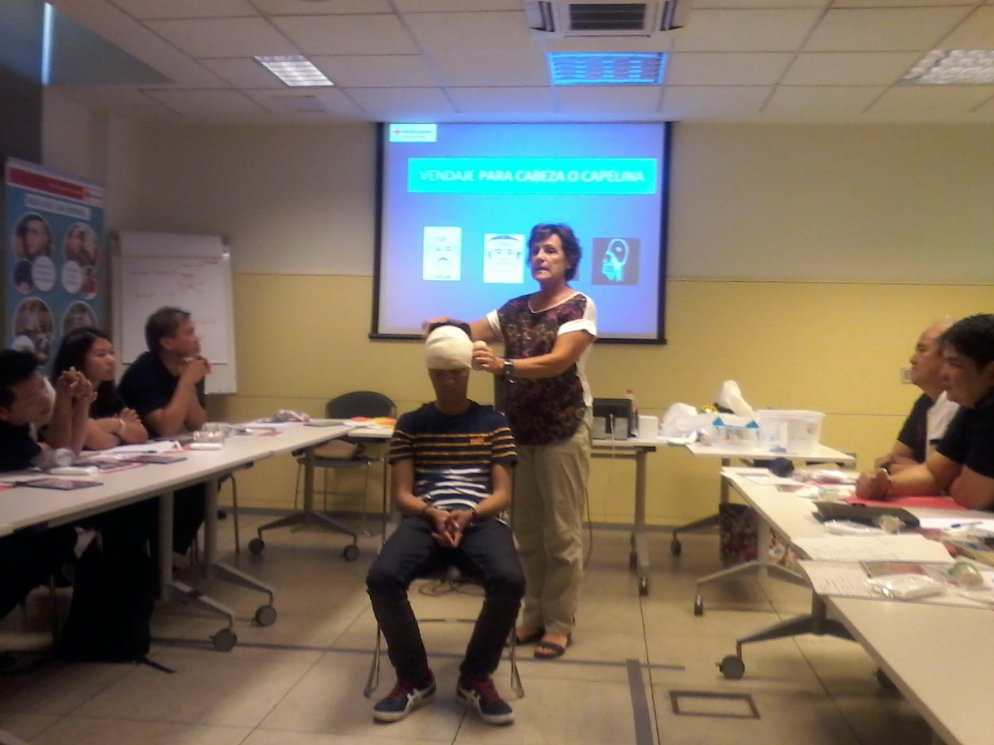 Esperanza Gemez demonstrates how to do a head bandage.
